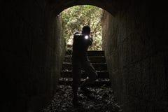 Вспугнутый человек с электрофонарем входит в тоннель Стоковые Фото