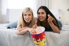 2 вспугнутых девушки смотря фильм Стоковые Фотографии RF