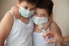 2 вспугнули братьев в медицинской маске смотря под рукой с шприцем Стоковое фото RF