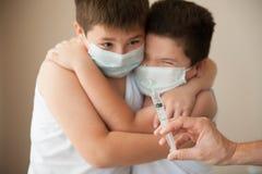 2 вспугнули детей в медицинской маске смотря под рукой с шприцем Стоковое Изображение RF
