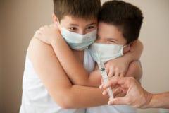 2 вспугнули мальчиков в медицинской маске смотря под рукой с шприцем Стоковое фото RF