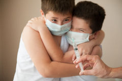 2 вспугнули мальчиков в медицинской маске смотря под рукой с шприцем Стоковые Фото