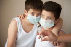 2 вспугнули мальчиков в медицинской маске смотря под рукой с шприцем Стоковые Изображения