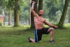 Вставать мышечный человек работая с Kettlebells Стоковые Фотографии RF