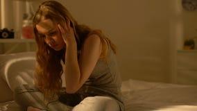 Встревоженное женское усаживание на кровати дома, интрузивные мысли, нервозность, тревога сток-видео