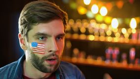 Встревоженный футбольный болельщик с американским флагом на щеке раздражанный с результатом игры видеоматериал