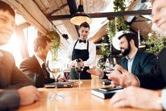 Встречать китайских бизнесменов в ресторане Кельнер льет вино в стеклах Стоковое Фото