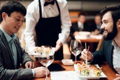 Встречать китайских бизнесменов в ресторане Кельнер приносит суши для того чтобы поставить на обсуждение стоковое изображение