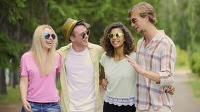 Встречать, молодые люди студент-выпускников смеясь над и имея потехой, обнимая один другого сток-видео