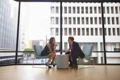 Встреча бизнесмена и женщины в современном офисе, во всю длину Стоковое фото RF