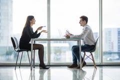 Встреча бизнесмена и коммерсантки в современном офисе лицом к лицу обсуждает планы Стоковые Изображения