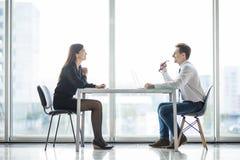 Встреча бизнесмена и коммерсантки в современном офисе лицом к лицу обсуждает планы Стоковые Фото