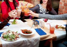 Встреча друзей женщин в ресторане для обедающего Девушки ослабляют и выпивают коктейли стоковое фото rf