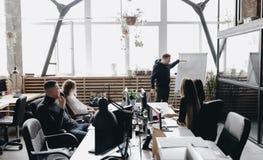 Встреча коллег Команда сидя на таблицах с компьютерами и ноутбуками и слушая к коллеге стоковое изображение rf