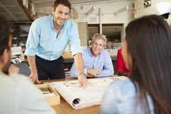 Встреча мужского босса ведущая архитекторов сидя на таблице стоковая фотография