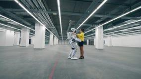 Встреча человека и киборга в комнате, обнимая один другого видеоматериал