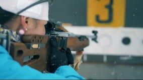 Всходы спортсмена биатлона при винтовка, стоя далеко от цели 4K сток-видео