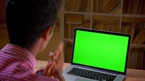 Всход взгляда крупного плана задний индийского молодого бизнесмена имея видео- звонок на ноутбуке с зеленым экраном chroma на сток-видео