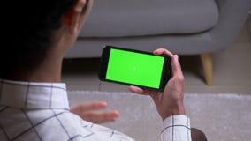 Всход взгляда крупного плана задний мужского имеющ видео- звонок и показывающ жестами держащ телефон с экраном зеленого chroma кл акции видеоматериалы