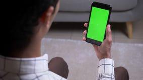 Всход взгляда крупного плана задний мужского имеющ видео- звонок с рукой держа телефон с зеленым экраном chroma внутри помещения  акции видеоматериалы