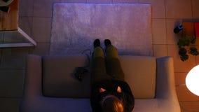 Всход крупного плана верхний довольно женских играя видеоигр на xbox используя консоль игры пока сидящ на кресле сток-видео