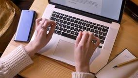 Всход крупного плана верхний женских рук печатая на ноутбуке внутри помещения в уютной кофейне сток-видео