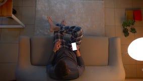 Всход крупного плана верхний молодого мужского смотря ТВ и использования приложения по телефону как дистанционное управление сидя акции видеоматериалы