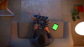 Всход крупного плана верхний молодого мужского смотря ТВ и использования приложения на планшете с зеленым экраном как дистанционн видеоматериал
