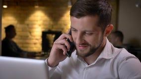 Всход крупного плана взрослого кавказского бизнесмена печатая на ноутбуке и имея случайный разговор по телефону жизнерадостно стоковая фотография rf