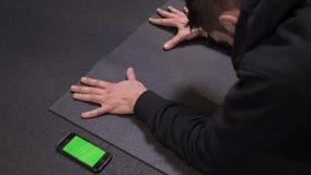 Всход крупного плана взрослого мышечного атлетического человека нажимая вверх с телефоном с зеленым экраном chroma лежа кроме вну сток-видео