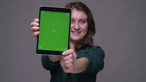 Всход крупного плана взрослого привлекательного брюнета женского используя планшет и показывать зеленому chroma ключевой экран с  сток-видео