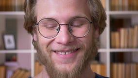 Всход крупного плана взрослого привлекательного студента в стеклах усмехаясь жизнерадостно смотрящ камеру в университетской библи акции видеоматериалы