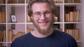 Всход крупного плана взрослого привлекательного студента в стеклах усмехаясь счастливо смотрящ камеру в университетской библиотек видеоматериал