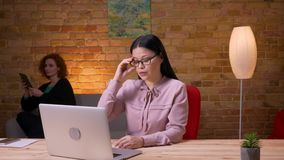 Всход крупного плана взрослой азиатской коммерсантки имея видео- звонок на ноутбуке внутри помещения в офисе Женский работник акции видеоматериалы