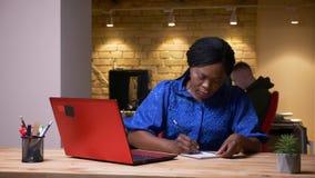 Всход крупного плана взрослой Афро-американской коммерсантки используя ноутбук и принимающ примечания в офис внутри помещения видеоматериал