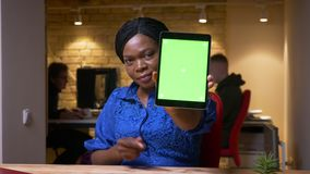 Всход крупного плана взрослой Афро-американской коммерсантки используя планшет и показывающ зеленый экран chroma к камере в акции видеоматериалы