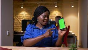 Всход крупного плана взрослой Афро-американской коммерсантки используя телефон и показывающ зеленый экран chroma к камере в акции видеоматериалы