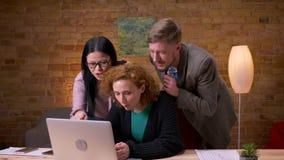 Всход крупного плана взрослой кавказской коммерсантки используя ноутбук внутри помещения в офисе 3 работника имея видео акции видеоматериалы