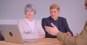 Всход крупного плана деловых партнеров женщины и людей имея встречу на обеде используя ноутбук сидя таблицей в сток-видео