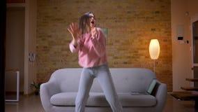 Всход крупного плана женщины молодого милого брюнета кавказской жизнерадостно играя на танцах Air Guitar и поя в уютном сток-видео