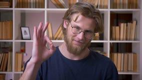 Всход крупного плана знака и смотреть взрослого привлекательного показа студента в порядке камеру в университетской библиотеке вн сток-видео