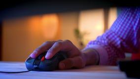 Всход крупного плана индийских мужских блоггеров вручает используя мышь компьютера внутри помещения в уютной квартире с неоновым  акции видеоматериалы