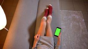 Всход крупного плана молодого женского блоггера моды используя телефон с зеленым экраном chroma Бедренные кости женщины в милом р стоковые фото