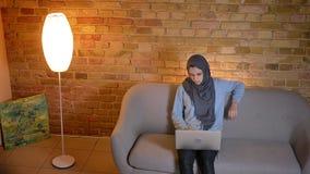 Всход крупного плана молодого жизнерадостного мусульманского женского подростка в hijab отправляя SMS на ноутбуке и имея видео- п видеоматериал