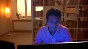Всход крупного плана молодого индийского привлекательного мужчины играя видеоигры на компьютере развлекая внутри помещения в уютн сток-видео