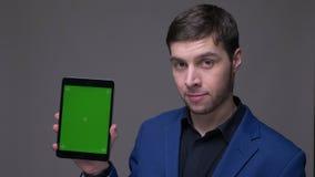 Всход крупного плана молодого красивого кавказского человека используя планшет и показывать зеленый экран к камере с предпосылкой видеоматериал