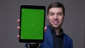 Всход крупного плана молодого красивого кавказского человека используя планшет и показывать зеленый экран chroma к камере с предп акции видеоматериалы