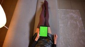 Всход крупного плана молодой женщины наблюдая видео на планшете с зеленым экраном chroma Связанные бедренные кости женщины в мило видеоматериал