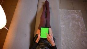 Всход крупного плана молодой женщины наблюдая видео на планшете с зеленым экраном chroma Связанные бедренные кости женщины в мило стоковая фотография rf