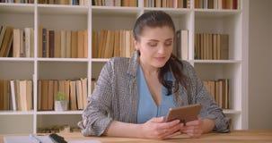Всход крупного плана молодой кавказской коммерсантки используя планшет в офисе библиотеки внутри помещения акции видеоматериалы
